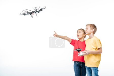 Photo for Children playing with flying hexacopter drone isolated on white - Royalty Free Image