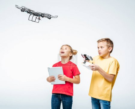 Photo for Happy kids using digital tablet and hexacopter drone isolated on white - Royalty Free Image
