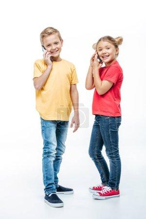 Photo pour Enfants heureux de parler sur les téléphones mobiles et regardant la caméra isolé sur blanc - image libre de droit