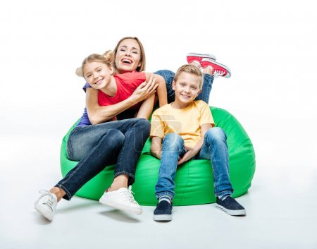 Photo for Happy mother with children having fun together in green sack-chair isolated on white - Royalty Free Image