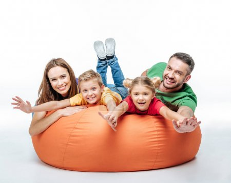 Photo for Happy family having fun together in sack-chair and looking at camera isolated on white - Royalty Free Image