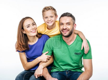 Photo for Young family in colorful t-shirts having fun and looking at camera isolated on white - Royalty Free Image
