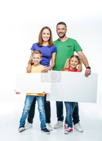 Photo for Smiling family standing with blank white cards in hands and looking at camera isolated on white - Royalty Free Image
