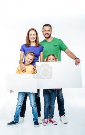 Foto de Smiling family standing with blank white cards in hands and looking at camera isolated on white - Imagen libre de derechos