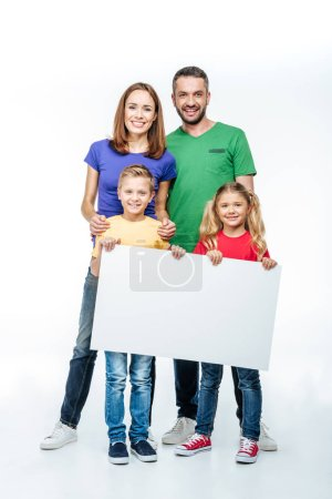 Photo for Smiling family standing with blank white card in hands and looking at camera isolated on white - Royalty Free Image