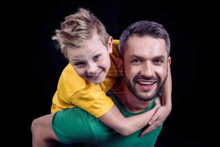 Photo for Smiling father piggybacking happy son and looking at camera isolated on black - Royalty Free Image