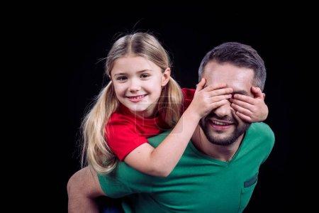 Photo for Smiling father piggybacking happy child isolated on black - Royalty Free Image