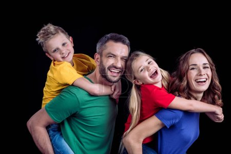 Photo for Happy family in colorful t-shirts hugging and smiling at camera isolated on black - Royalty Free Image