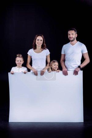 Photo pour Famille souriante debout avec une carte blanche vierge et regardant la caméra isolée sur noir - image libre de droit