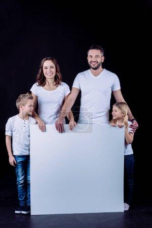 Photo pour Famille souriante en t-shirts blancs tenant carte blanche vierge et regardant la caméra isolée sur noir - image libre de droit