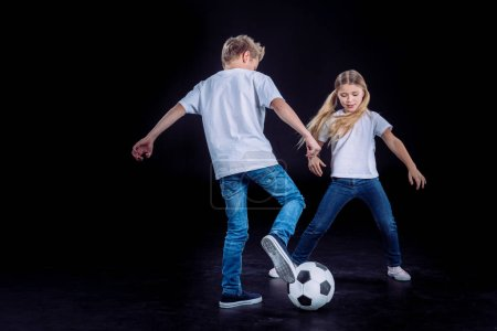 Brother and sister playing with soccer ball