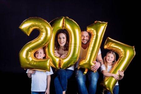 Photo pour Joyeux famille tenant doré 2017 signe ballons et regarder la caméra isolée sur noir - image libre de droit
