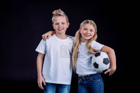 Photo pour Front view of happy brother and sister posing with soccer ball isolated on black - image libre de droit