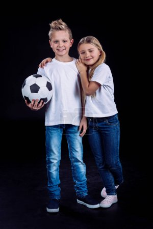 Brother and sister posing with soccer ball
