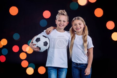 Foto de Front view of happy brother and sister posing with soccer ball isolated on black - Imagen libre de derechos