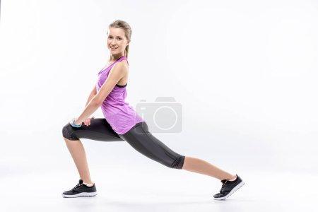 Photo pour Femme sportive étirant et regardant la caméra isolée sur blanc - image libre de droit