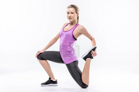 Photo for Sporty woman in sportswear stretching legs and looking at camera isolated on white - Royalty Free Image