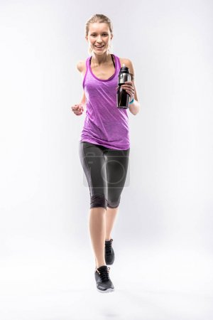 Photo for Athletic blonde woman running with sports bottle and smiling at camera - Royalty Free Image