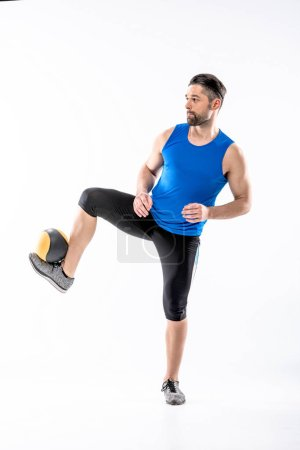 Photo for Athletic man in sportswear exercising with ball isolated on white - Royalty Free Image