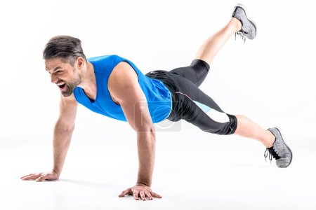 Photo for Full length portrait of young athletic man doing plank exercise isolated on white - Royalty Free Image