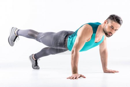 Photo pour Muscular man doing plank exercise and looking at camera isolated on white - image libre de droit