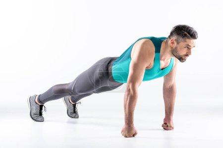 Photo pour Homme sportif en tenue de sport faisant de l'exercice de planche isolé sur blanc - image libre de droit