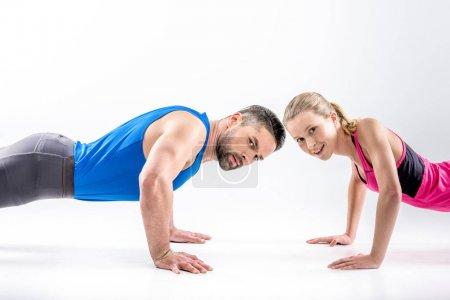 Photo pour Couple sportif faisant des pompes et regardant la caméra - image libre de droit