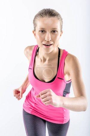 Photo pour Jeune femme en jogging de vêtements de sport et en regardant la caméra isolée sur blanc - image libre de droit