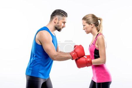 Photo pour Homme et femme en gants de boxe en colère se regardant isolés sur blanc - image libre de droit