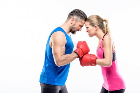 Photo for Man and woman in boxing gloves angry looking at each other isolated on white - Royalty Free Image