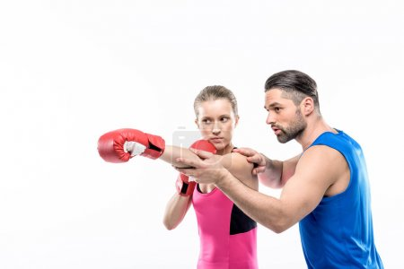 Girl practicing boxing with trainer