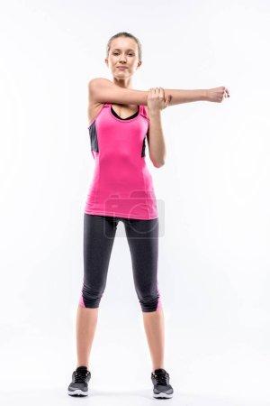 Photo pour Jeune femme en tenue de sport étirant les bras et regardant la caméra isolée sur blanc - image libre de droit