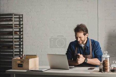 Photo for Smiling man in apron working with laptop at the bakery - Royalty Free Image