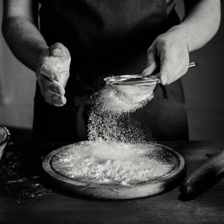 Photo for Partial view of baker in apron sifting flour, black and white photo - Royalty Free Image