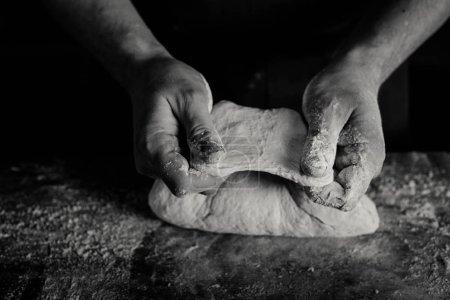 Baker examining dough