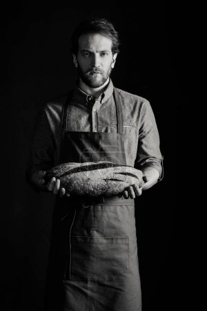 Photo for Male baker holding bread loaf and looking at camera, black and white photo - Royalty Free Image