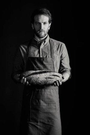 Photo pour Boulanger masculin tenant pain pain et regardant appareil photo, photo noir et blanc - image libre de droit