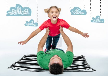 Photo for Happy father and daughter having fun together while lying on drawn carpet - Royalty Free Image