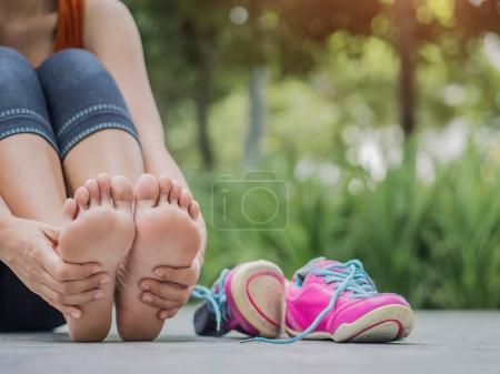 Photo for Closeup woman massaging her painful foot while exercising.   Running sport injury concept. - Royalty Free Image
