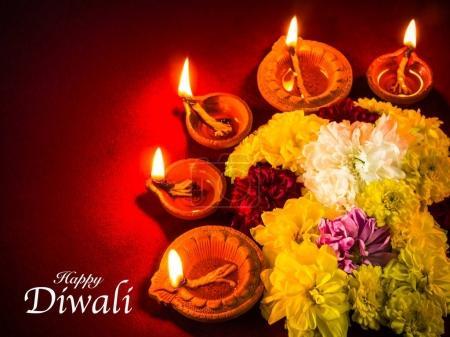 Photo pour Lampes traditionnelles diya en argile allumées avec des fleurs pour la célébration du festival Diwali . - image libre de droit