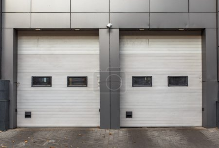 Two white garage doors. Sectional lift gates.