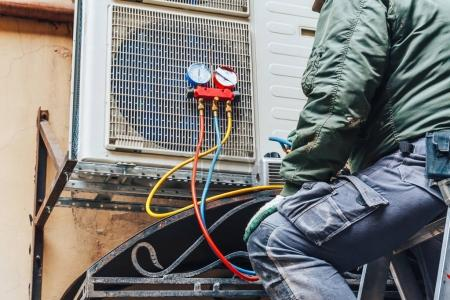 Photo for Worker repairs air conditioner on the wall, Air Conditioning Repair concept - Royalty Free Image