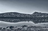 Landscape wonderful of rocky hills reflected in the clean quiet lake painted black and white