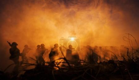 Photo pour Concept de la guerre. Militaire silhouettes combat scène sur fond de ciel brouillard guerre, guerre mondiale soldats Silhouettes ci-dessous nuageux Skyline au crépuscule ou à l'aube. Scène de l'attaque - image libre de droit