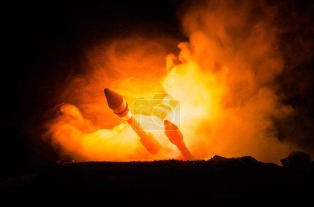 Lanzamiento de cohetes con nubes de fuego. Misiles nucleares con ojiva apuntada al cielo sombrío por la noche. Balistic Rockets War Backgound (en inglés). Alerta de guerra mundial