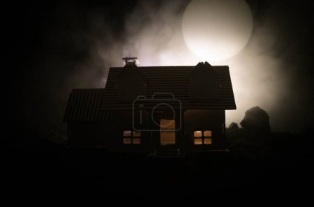 Photo for Old house with a Ghost in the moonlit night or Abandoned Haunted Horror House in fog. Old mystic villa with surreal big full moon. Horror Halloween concept. - Royalty Free Image