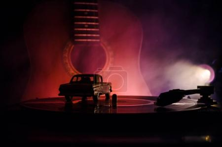 Photo for Vintage vinyl record playing on player and acoustic guitar on background with fire orange smoke. Blues concept. With Toy car - Royalty Free Image
