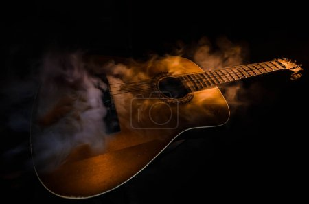 Photo for Music concept. Acoustic guitar isolated on a dark background under beam of light with smoke with copy space. Guitar Strings, close up. Selective focus. Fire effects. Surreal guitar - Royalty Free Image