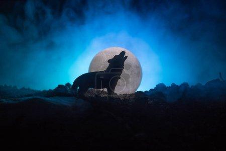 Photo pour Silhouette de loup hurlant sur fond brumeux foncé et pleine lune ou loup en silhouette hurlant à la pleine lune. Concept d'horreur Halloween. Concentration sélective - image libre de droit
