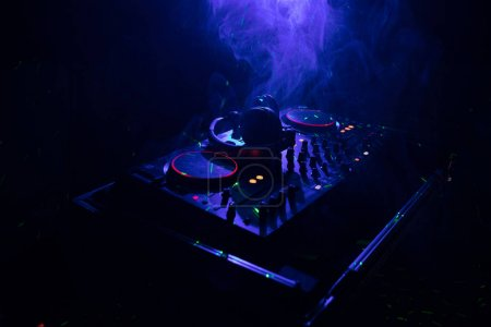 Photo pour Filature de DJ, mixage et gratter dans un Night-Club, mains de dj tweak diverses commandes de piste sur le pont du dj, lumières stroboscopiques et le brouillard, ou Dj mixes la piste dans la boîte de nuit au parti. Mise au point sélective - image libre de droit